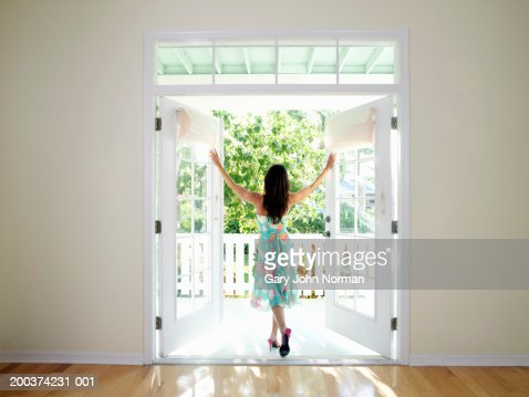Woman standing in doorway with arms stretched out, rear view : Stock Photo