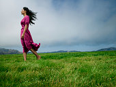 Woman standing in grass field barefoot, wind blowing in hair