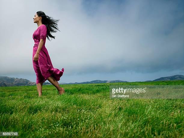Woman standing in field barefoot