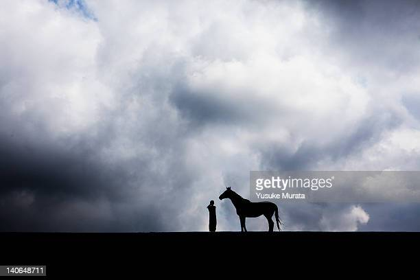 Woman standing in field with horse