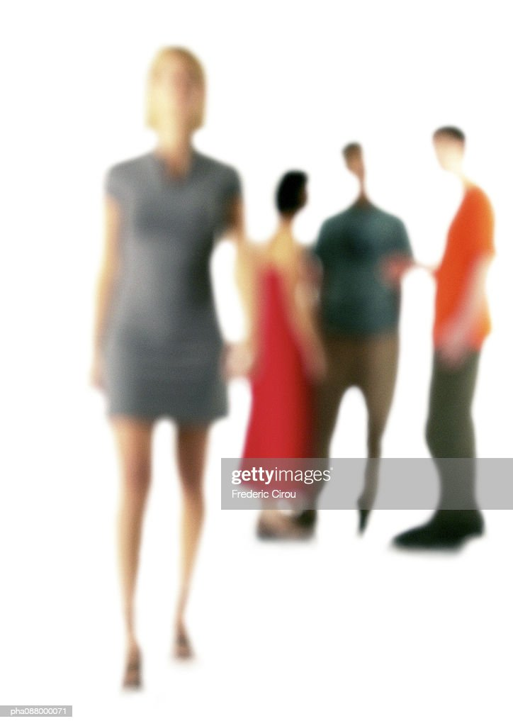 Woman standing in foreground, three people standing together in background, defocused : Stock Photo