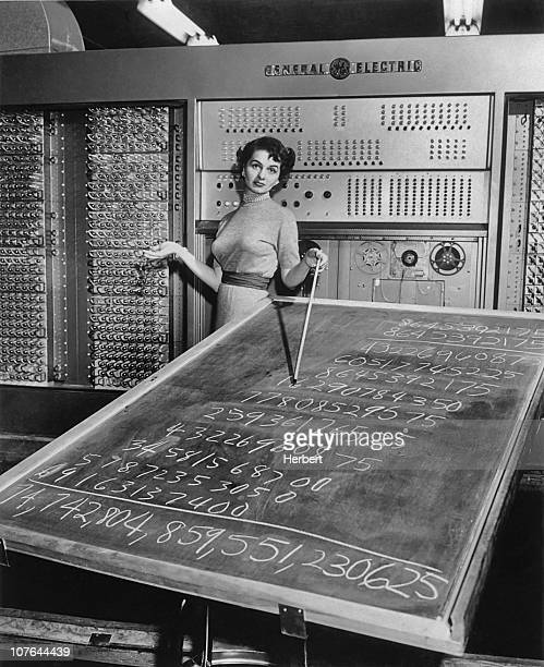 A woman standing in front of a General Electric mainframe computer and pointing to a complex calculation on a blackboard circa 1955
