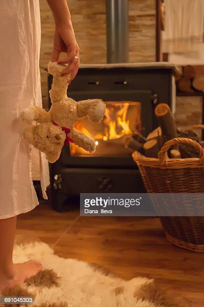 Woman standing in front of a wood burner holding a teddy bear