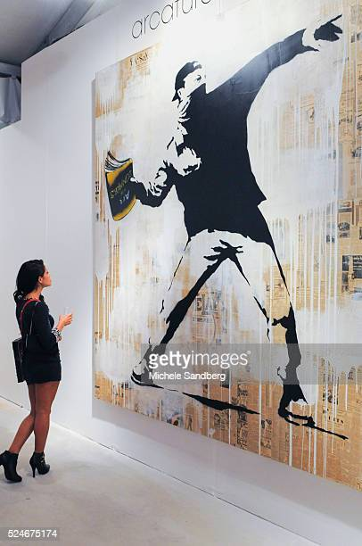 A woman standing in front of Artist Bansky's artwork called Bansky Thrower at Art Miami during Art Basel Week