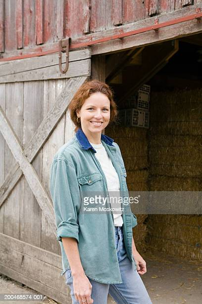 Woman standing in front of barn filled with hay, smiling, portrait