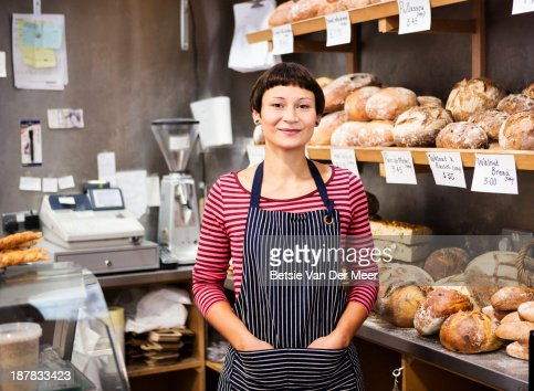 woman standing in front of bread display.