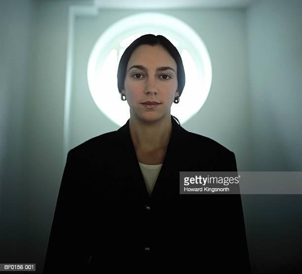 Woman standing in front of door with circular window, portrait