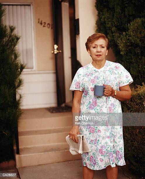 Woman standing in front of house, holding cup and newspaper, portrait