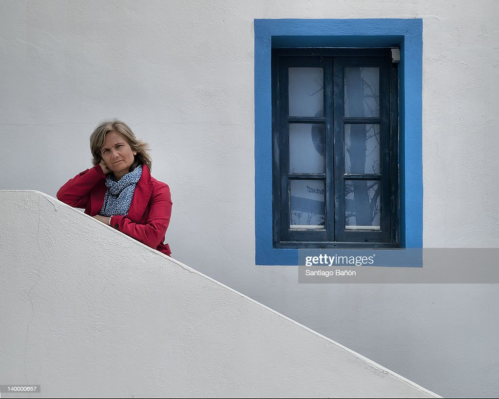 Woman standing in front of house : Stock Photo