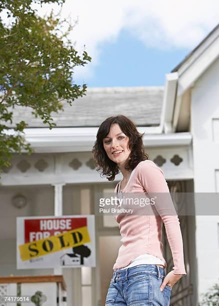 Donna in piedi davanti a casa con segno venduto