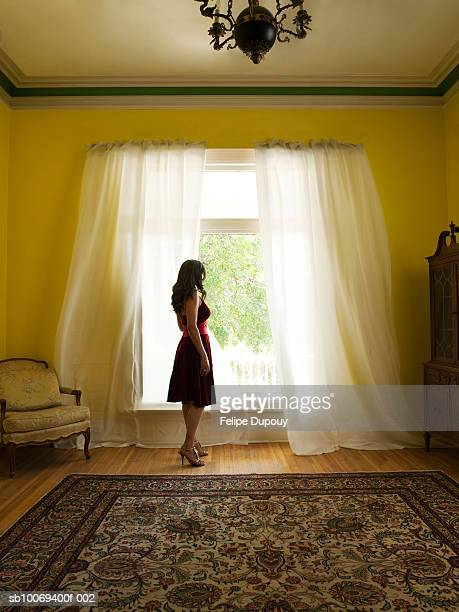 Woman standing in front of large window with billowing curtains