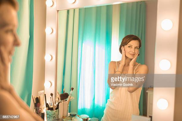 Woman standing in front of mirror at dressing table