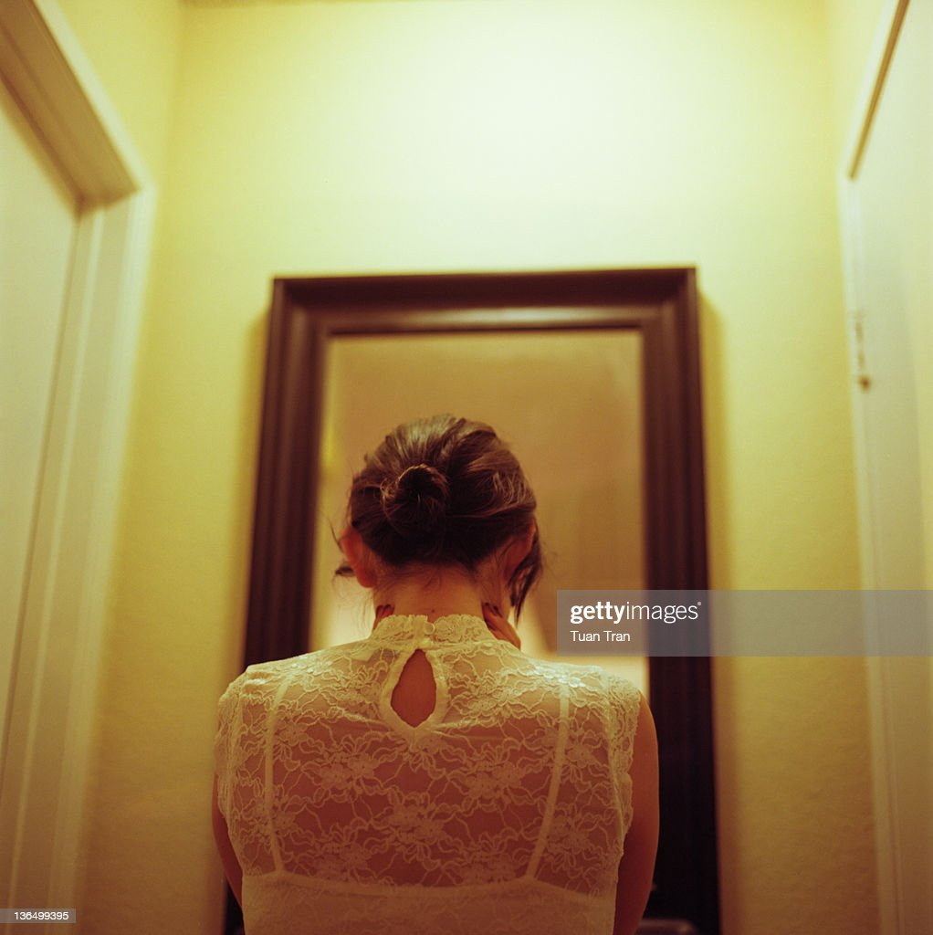 Woman standing in front of mirror : Stock Photo