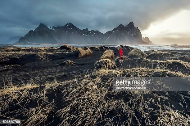 Woman standing in front of mount vestrahorn, Hornafjordur, Iceland