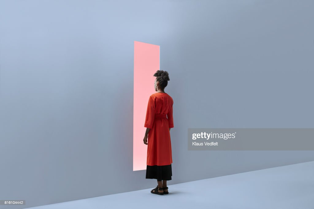 Woman standing in front of rectangular opening in coloured wall : Stock Photo