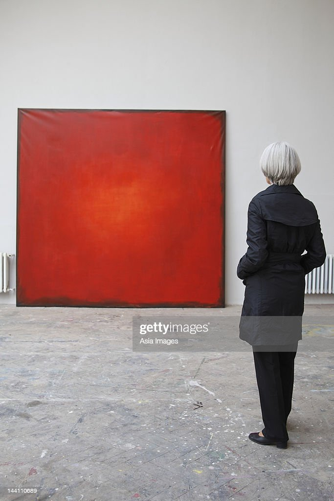 woman standing in front of red painting : Stock Photo