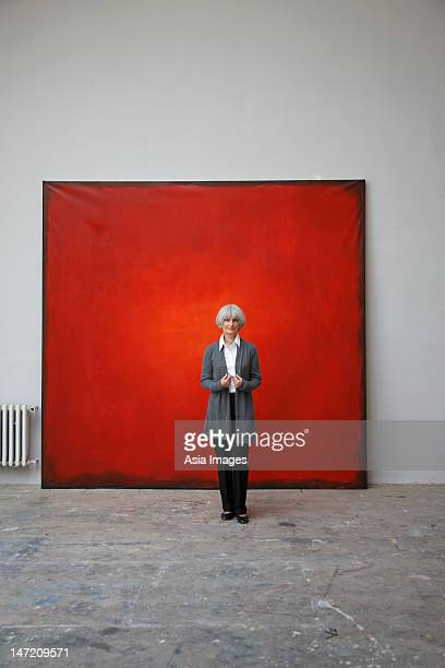 woman standing in front of red painting