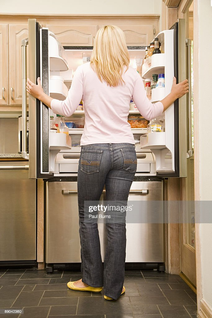 Woman Standing in Front of Refrigerator in Kitchen : Stock Photo