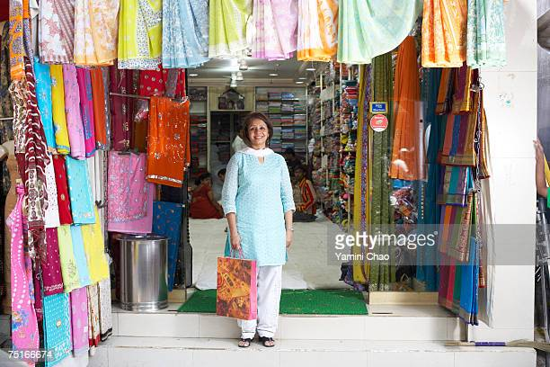 Woman standing in front of sari shop, portrait