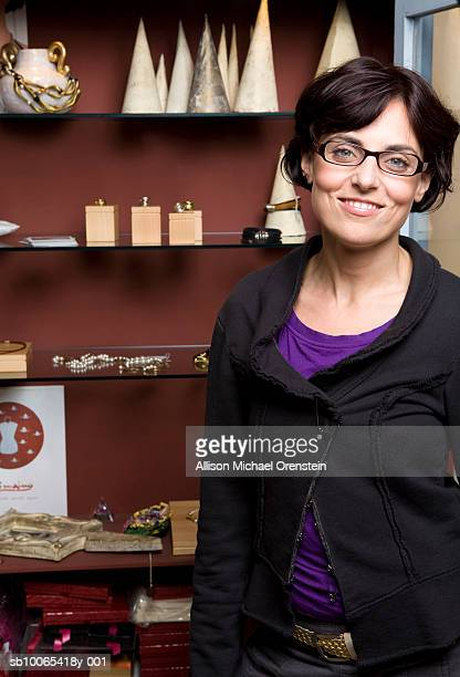 Woman standing in front of shelf with jewellery, portrait