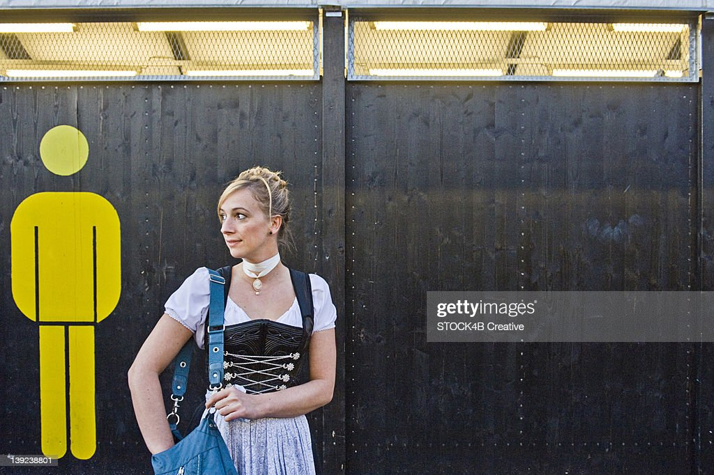 Woman standing in front of the men's restroom on the Oktoberfest in Munich, Bavaria, Germany