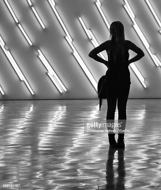 Woman Standing In Front Of Wall With Illuminated Fluorescent Lights