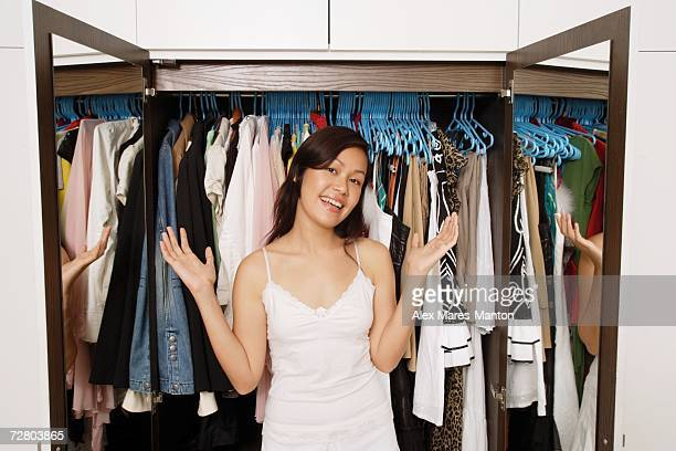 Woman standing in front of wardrobe full of clothes, smiling at camera