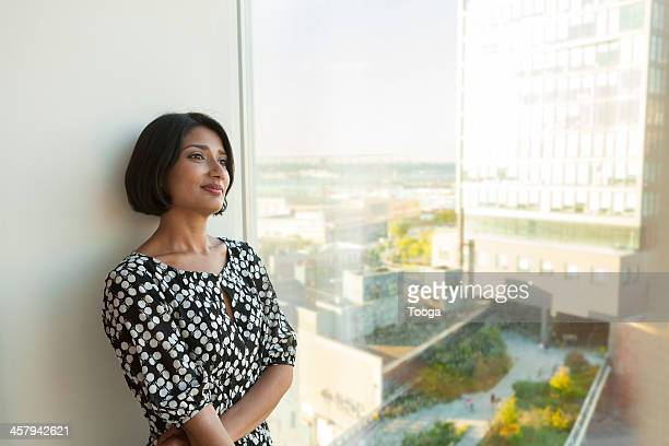 Woman standing in front of window pensive