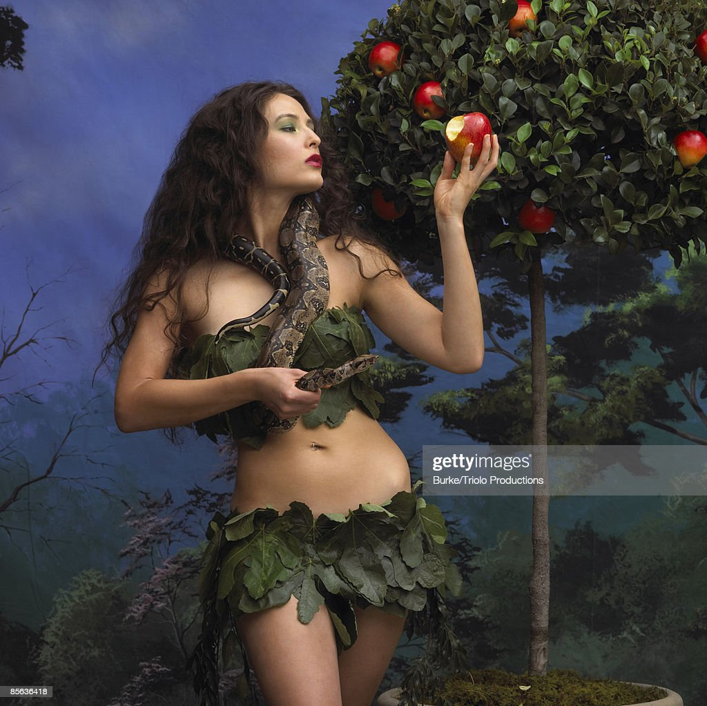 Woman standing in garden holding snake and apple