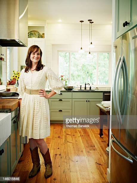 Woman standing in home kitchen hand on hip smiling