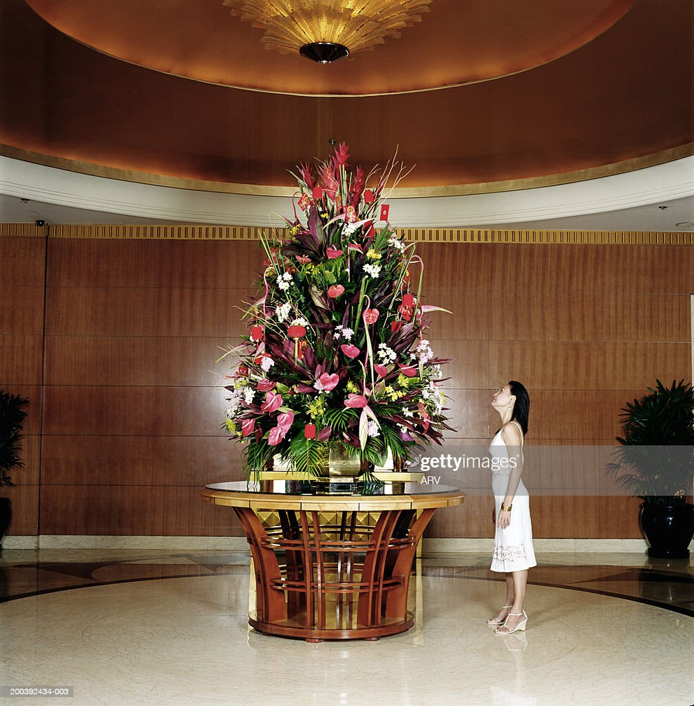 Foyer In Hotel : Woman standing in hotel foyer looking up at flower