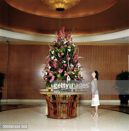 Woman standing in hotel foyer looking up at flower for Foyer flower arrangement