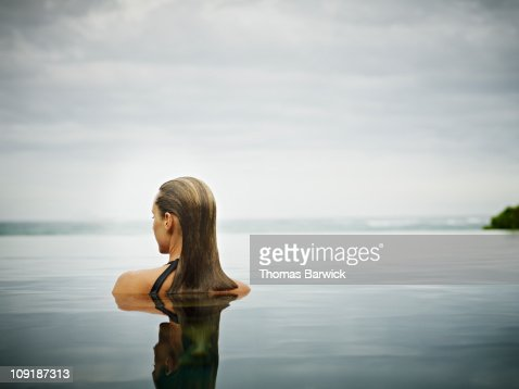 Woman standing in infinity pool overlooking ocean : Stock Photo