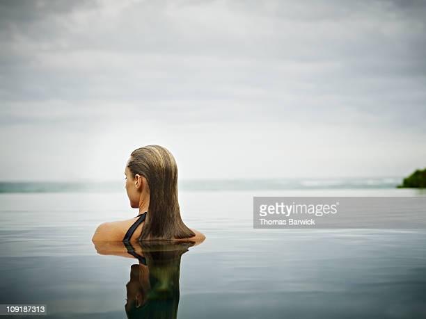 Woman standing in infinity pool overlooking ocean