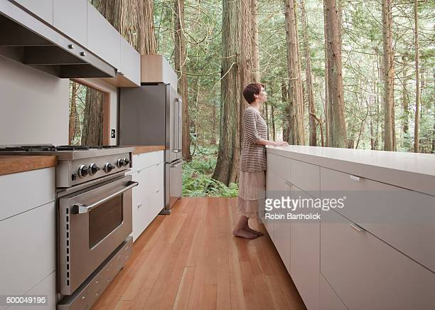 Woman standing in kitchen in forest