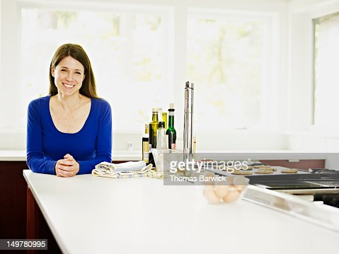 Woman standing in kitchen leaning on counter : Stock Photo