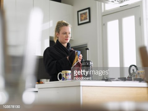 Woman standing in kitchen, low angle view : Stock Photo