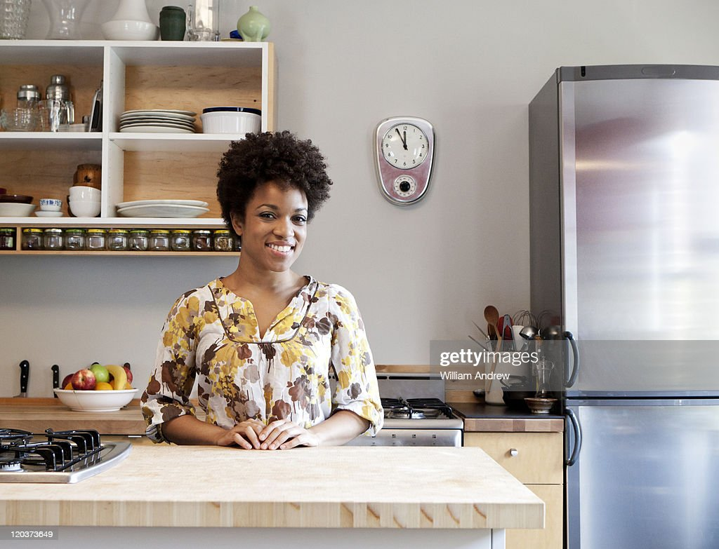 Woman standing in kitchen, smiling : Stock Photo