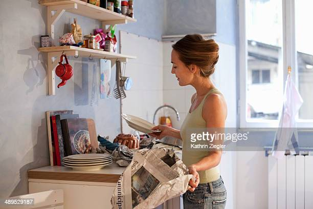 woman standing in kitchen, unwrapping dishes