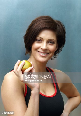 Woman standing in locker room holding apple : Photo