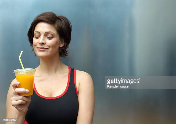 Woman standing in locker room holding orange juice