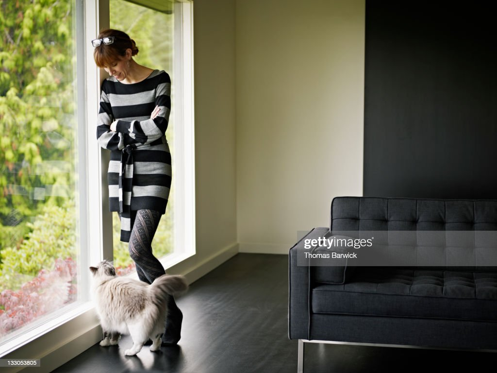 Woman standing in looking at cat at her feet : Stock Photo