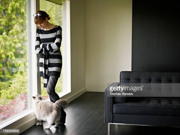 Woman standing in looking at cat at her feet