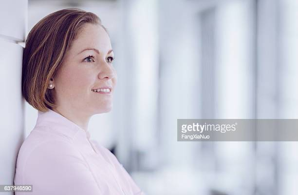 Woman standing in modern office looking forward