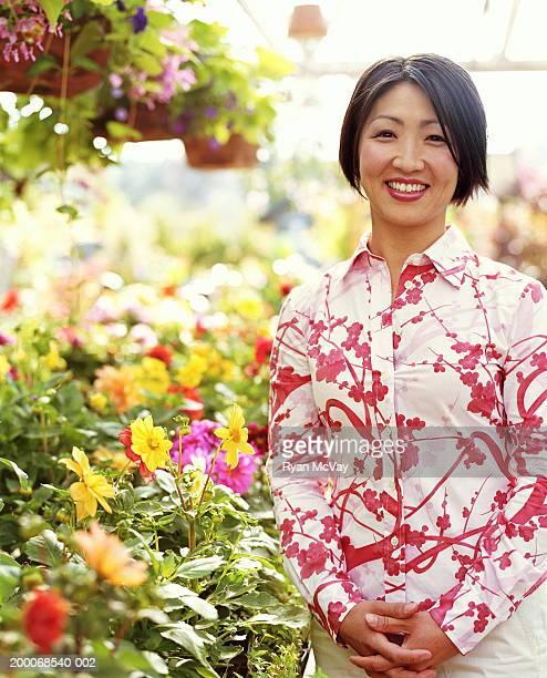 Mujer de pie en un jardín de infancia, rodeado de plantas, portr cornejo