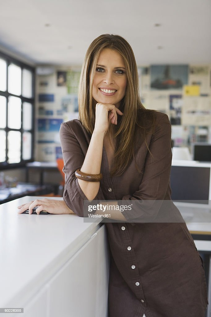 Woman standing in office, smiling, portrait : Stock Photo
