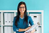 Young business woman standing in office with folder