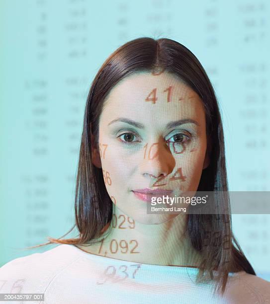 Woman standing in overhead projector light, portrait