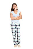 Woman standing in pajamas smiling isolated on white background in full length. Mixed race Asian / Caucasian female model.