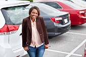 African American woman (30s) standing in parking lot.  Shallow DOF, focus on foreground.